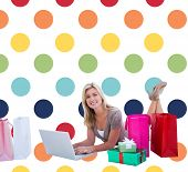 Happy blonde shopping online with laptop against colorful polka dot pattern