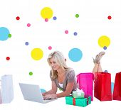 Happy blonde shopping online with laptop against dot pattern