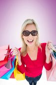Happy blonde holding shopping bags on vignette background