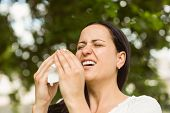 Sick brunette holding tissue sneezing in the park