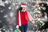 Happy brunette in winter wear holding shopping bags against shimmering christmas tree of lights