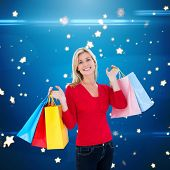 Happy blonde holding shopping bags against bright star pattern on blue