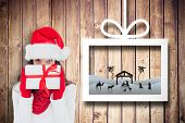 Brunette in red gloves and santa hat showing gift against christmas decorations over wood