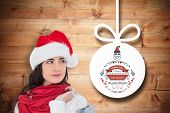 Brunette in santa hat holding shopping bag against christmas decorations over wood
