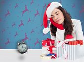 Brown hair in santa hat napping against blue and purple reindeer pattern