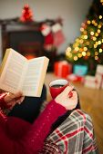 Woman in jumper reading and drinking coffee at christmas in the living room