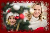 Festive mother and daughter decorating christmas tree against snowflake frame