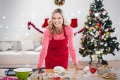 Festive blonde making christmas cookies against snow