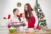 Festive mother and daughter baking together against twinkling stars