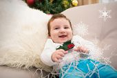 Cute baby boy on the couch at christmas against hanging snowflakes