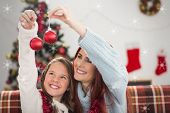 Festive mother and daughter holding baubles against snowflakes