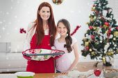 Festive mother and daughter baking together against snow
