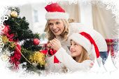Festive mother and daughter decorating christmas tree against frost frame
