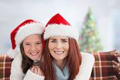 Mother and daughter against blurry christmas tree in room