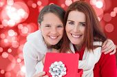 Mother and daughter with gift against digitally generated twinkling light design