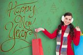 Brunette in winter clothes holding shopping bags against green christmas tree pattern