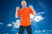 Mature man in orange tshirt cheering against cloudy sky with sunshine