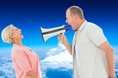 Man shouting at his partner through megaphone against mountain peak through the clouds