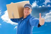 Happy delivery man holding cardboard box against cloudy sky