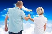 Happy older couple painting white wall against bright blue sky with clouds