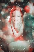 Festive little girl in hat and scarf against candle burning against festive background