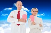 Older couple standing holding broken pink heart against bright blue sky with clouds