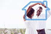 Romantic couple dancing and smiling against house outline