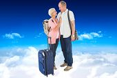 Smiling older couple going on their holidays against bright blue sky over clouds