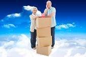 Older couple smiling at camera with moving boxes and piggy bank against bright blue sky with clouds