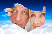 Older couple looking through rip against bright blue sky with clouds