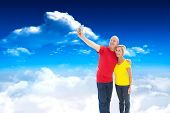 Happy mature couple taking a selfie together against bright blue sky with clouds