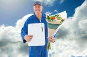 Happy flower delivery man showing clipboard against blue sky with clouds