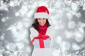 Festive brunette in santa hat giving gift against shimmering light design on grey