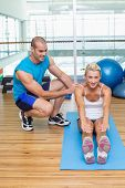 Male trainer assisting young woman with exercises at fitness studio