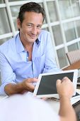 Closeup of businessman having client signing contract on tablet
