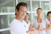 Mature man amongst group doing yoga exercises
