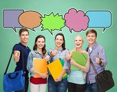 school, education, communication and people concept - group of smiling teenagers with folders and school bags showing thumbs up over green board background with text bubbles
