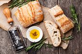 stock photo of virginity  - Sliced bread Ciabatta and extra virgin Olive oil on wooden background - JPG