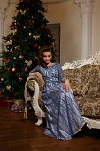 Fashion Woman Sitting On Sofa In Front Of Christmas Tree