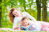 Mom And Daughter Reading A Book Lying In The Park