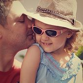 Happy Father Kissing His Daughter In Fashion Glasses And Hat