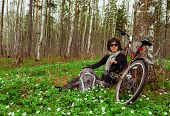 Young woman cyclist resting in forest