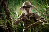 picture of machete  - Watchful young adventurer holding a machete walking through the jungle - JPG