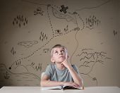 stock photo of treasure map  - Little kid thinking about treasure map from his adventure book - JPG