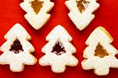 stock photo of linzer  - Linzer cookies in shape of Christmas tree on red background - JPG