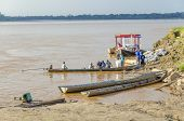 RURRENABAQUE, BOLIVIA, MAY 10, 2014 - Local people work  in traditional wooden boats on Beni river