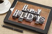 Happy Holidays greetings  in vintage metal type printing blocks on a digital tablet with a cup of coffee