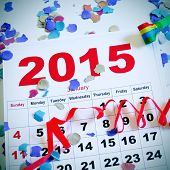 a january 2015 calendar on a white surface full of confetti, streamers and a party horn
