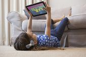 Little girl using digital tablet in the living room against colourful happy new year