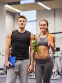 fitness, sport, people and lifestyle concept - happy couple in gym with water, towel and tablet pc computer